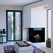 Open fireplace next to French windows in elegant living room