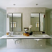 Large double washstand with asymmetrically divided mirrors on concrete partition and doors to floor-level shower on either side