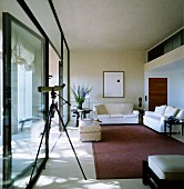 Purist interior with seating area on matte rug next to glass wall and telescope in foreground