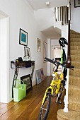 Folding bike at foot of stairs in hall of London house with collection of pictures on wall