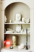 Carved figurines and clarinet in old, classic fitted shelves in niche