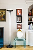 Designer standard lamp and nest of plexiglass tables below collection of paintings on wall