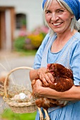 Germany, Bavaria, Mature woman with basket of fresh eggs and chicken