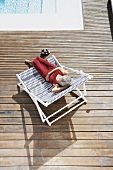 Spain, Senior woman relaxing on deck chair at beach