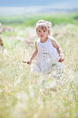 Blonde little girl walking through tall grass