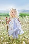 Little girl standing in summer meadow