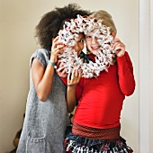 Girls looking through a Christmas wreath