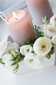 White ranunculus and lit candle in white dish