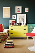 Yellow chest of drawers against grey wall below collection of pictures; armchair with floral upholstery and white designer swivel chair with red cushion in foreground