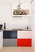 Minimalist kitchen with colorful panels on the lower cabinets under a built-in extractor fan with integrated shelves