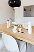 Asian crockery on a wooden table in front of a kitchen pass through in a minimalist kitchen