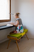 Lady sitting on a bench with a green pad at a minimalist table in front of a window