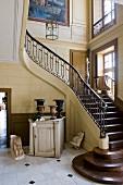 Foyer mit gewendeltem Treppenaufgang und pokalartige Gefässe auf halbhohem Vintage Schrank in Herrenhaus