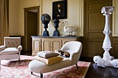 Chaise longue with white cover in front of massive stone flower pedestal in antique Greek style and armchair in grand salon
