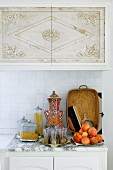 Plate of fruit and Moroccan tea glasses on marble worksurface of kitchen counter in front of tiled splashback below wall units with Oriental pattern on doors