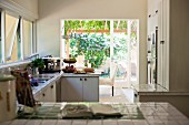 View across tiled kitchen counter into open-plan kitchen with view of garden through terrace doors
