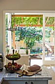 Fruit stand on tiled kitchen counter in front of open terrace door with view into small front garden