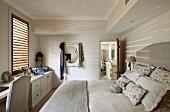 Double bed with upholstered headboard and ecru bed linen in simple bedroom with open door leading to bathroom