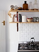 Storage jars and kitchen utensils on wooden kitchen shelves above retro gas hob