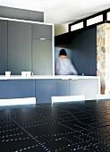 Puristische Einbauküche in Grau; schwarze Tischplatte mit Lochmuster im Vordergrund