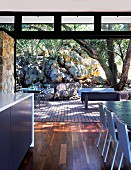 Sliding doors without threshold between dining area and wooden terrace; outdoor seating area sheltered by boulders