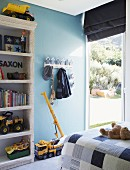 Child's bedroom with bed, shelves of toys & terrace door with Roman blind