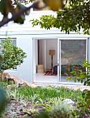 View from garden through open sliding terrace doors into bedroom