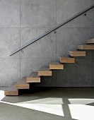 Floating wooden stair treads on exposed concrete wall and stainless steel handrail