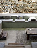 Sunken, concrete seating area with seat cushions and scatter cushions against stone wall