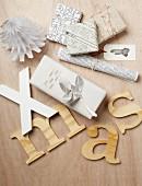 Besondere Verpackungsidee mit Zeitungspapier in verschiedenen Sprachen, Bastelblumen aus bedrucktem Papier und Deko-Buchstaben