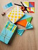 Artistically wrapped gifts using self-adhesive dots, coloured strips of notepaper and tangram-style coloured shapes