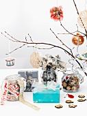 In dezenten Naturfarben weihnachtlich geschmückte Zweige, Einmachgläser mit Dekowaren und Geschenkpäckchen