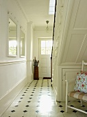 Hall with tiled floor, white-painted wooden staircase, white walls and wall mirrors