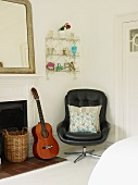Swivel chair, guitar, wall-mounted shelves and open fireplace in corner of room