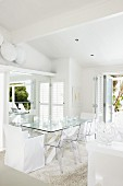Dining area with transparent, plastic chairs and chair with white loose cover around glass table in designer interior