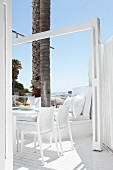 Holiday atmosphere - terrace with white outdoor furniture on white wooden floor with integrated palm tree trunks