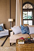 Wicker coffee table in front of sofa with scatter cushions and arched window in grand interior
