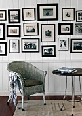 Wicker chair against white wooden wall with large collection of black-framed photographs