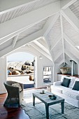 Light-flooded living room of beach house with wooden pavilion roof and magnificent view of rocky coast