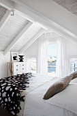 Relaxing holiday atmosphere in white bedroom with view of sea and rocks