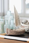Hand-crafted sailing boat ornament on book