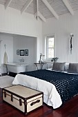 Bedroom with vintage trunk at foot of large double bed and ensuite bathroom with antique bathtub