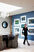 Modern artworks on blue wall; round dining table and chairs with patterned loose covers below large skylight