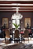 Modern African art and huge vase of leaves in palatial dining room with zebra-skin rug and crystal chandelier