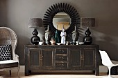 Objets d'art and table lamps with fur lampshades on shabby chic sideboard below black sunburst mirror