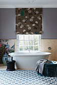 Picture of bird leaning on wall and Chinese porcelain vase next to free-standing bathtub below lattice window in bright bathroom