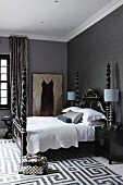 Grey bedroom with artistic, Chinese double bed with tall, silver-ornamented bedposts; rug with woven, geometric pattern on floor