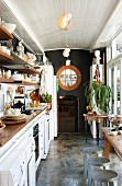 Narrow kitchen with black-painted end wall and metal bar stools next to kitchen table and terrace window