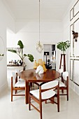 Retro wooden table and chairs with white cushions in renovated period building with stately ambiance