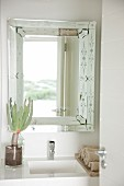 Landscape reflected in bathroom mirror; succulent in glass vase on sink surround